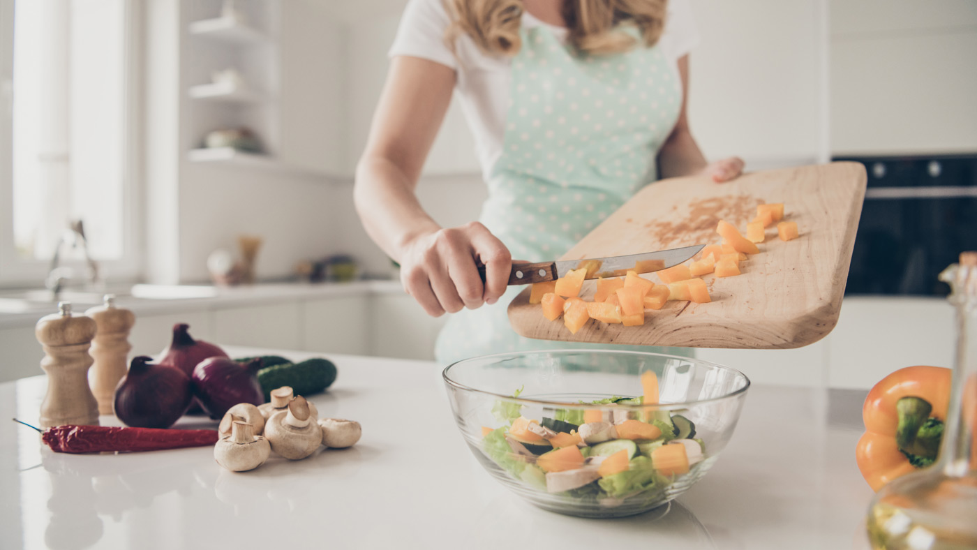 Cropped view of wavy-haired lady putting in bowl slices pieces m